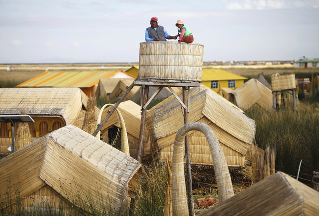 An Andean man and a child stand at the top of a tower in a Uros island at Lake Titicaca in Puno November 5, 2014. (Photo by Enrique Castro-Mendivil/Reuters)