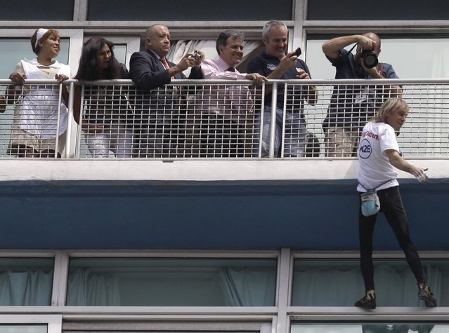 Alain Robert, holds on to a 20th floor railing as he pauses to wave to tourists and onlookers below, during his ascent to the top of the Habana Libre hotel without using ropes or a safety net, in Havana, Cuba, Monday, February 4, 2013. Once the city's Hilton, Robert was able to reach the top of the 27-story building in 30 minutes. Robert has scaled much taller buildings in his career. He says his main concern is that the hotel is in disrepair like other Havana landmarks. (AP Photo/Franklin Reyes)