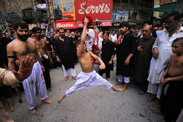 A young Shiite Muslim boy holds knives attached to chains as he flagellates, during Ashura Day procession in Peshawar, Pakistan, 30 August 2020. Shiite Muslims are observing the holy month of Muharram, the climax of which is the Ashura festival that commemorates the martyrdom of Imam Hussein, a grandson of the Prophet Mohammed, in the Iraqi city of Karbala in the seventh century. (Photo by Arshad Arbab/EPA/EFE)