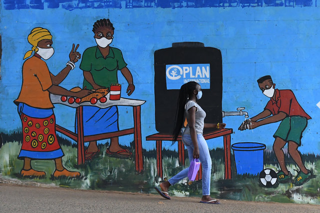 A woman with a face mask walks past graffiti that promotes hand washing and wearing face masks as preventive measures against the spread of the COVID-19 coronavirus, in Kibera, Nairobi, on August 13, 2020. (Photo by Simon Maina/AFP Photo)