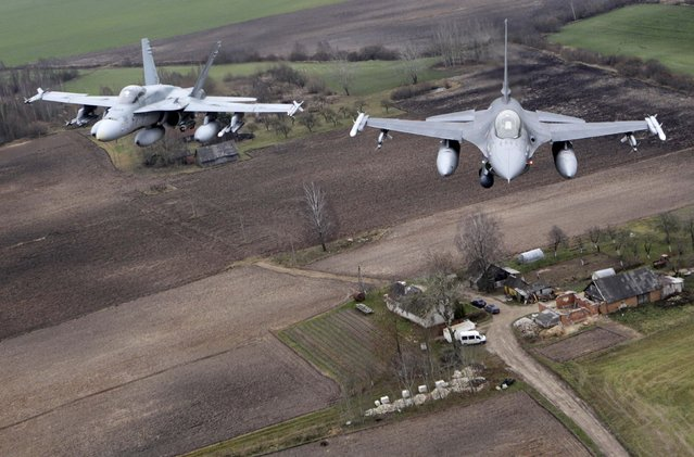 Portuguese Air Force fighter F-16 (R) and Canadian Air Force fighter CF-18 Hornet patrol over Baltics air space, from the Zokniai air base near Siauliai November 20, 2014. NATO pilots practised scrambling their jets on Wednesday, in preparation for potential further unauthorised Russian jets encountered on Baltic patrols. (Photo by Ints Kalnins/Reuters)