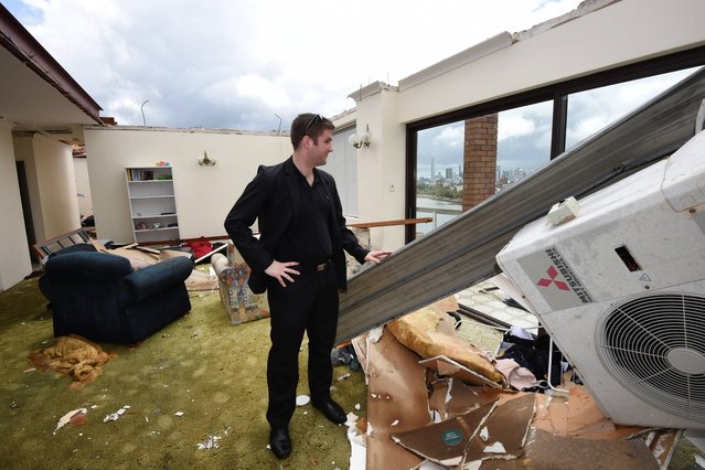 James Marriott surveys the damage in his roofless apartment, Friday, November 28, 2014, in the inner city suburb of Toowong in Brisbane, Australia, after a severe thunderstorm swept through the city Thursday. Australia's third-largest city, was lashed by its worst storm in decades, with wind, rain and hail lifting roofs, cutting power lines, flooding streets and injuring a dozen people, officials said. (Photo by Dan Peled/AP Photo/AAP Image)