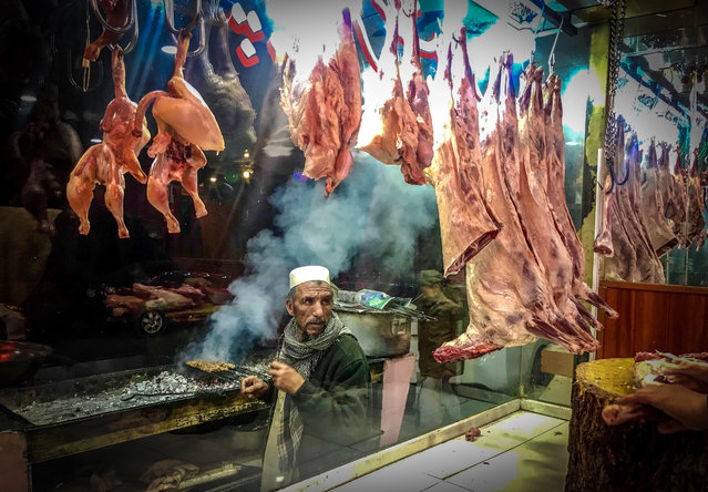 A man sells traditional grilled food at a shop in Kabul, Afghanistan, 12 January 2018. (Photo by Hedayatullah Amid/EPA/EFE)