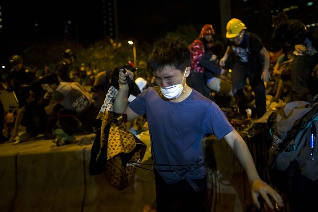 A pro-democracy protester reacts to pepper spray, as riot police attempt to clear a demonstration site close to the chief executive office in Hong Kong December 1, 2014. (Photo by Tyrone Siu/Reuters)