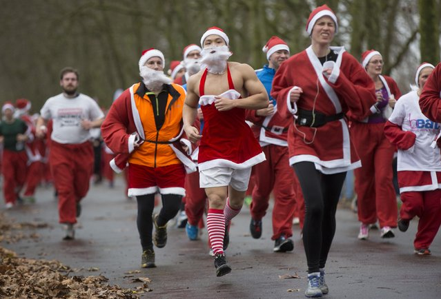 Runners dressed in Santa Claus outfits compete in the annual Santa Run in Victoria Park, east London December 7, 2014. (Photo by Neil Hall/Reuters)