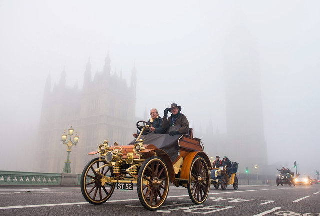 Participants in the London to Brighton Veteran Car Run, cross Westminster Bridge in London, with the houses of parliament partially seen through the morning fog, in London, Sunday November 1, 2015. The London to Brighton Veteran Car Run is a long running traditional event only cars built before January 1, 1905, eligible to take part in the 54 miles (87 km) route, watched by thousands of onlookers. (Photo by Dominic Lipinski/PA Wire via AP Photo)