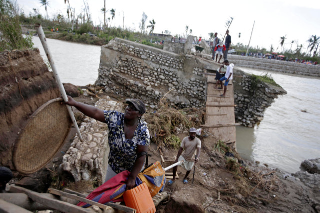 People use a handmade ladder after the bridge has been destroyed by Hurricane Matthew in Chantal, Haiti October 7, 2016. (Photo by Andres Martinez Casares/Reuters)