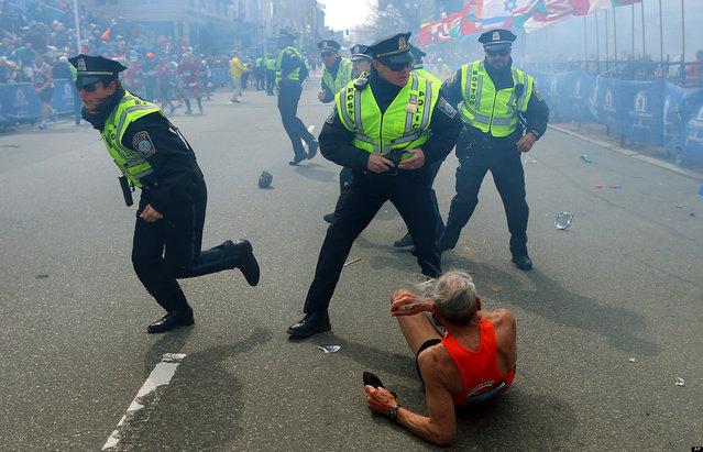Police officers react to a second explosion at the finish line of the Boston Marathon in Boston, Monday, April 15, 2013. (Photo by John Tlumacki/AP Photo/The Boston Globe)