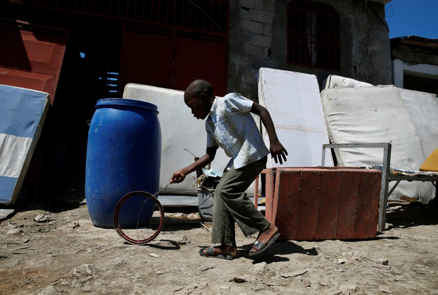 A child plays hoop rolling as mattresses are set out to dry after Hurricane Matthew passes in Jeremie, Haiti, October 8, 2016. (Photo by Carlos Garcia Rawlins/Reuters)