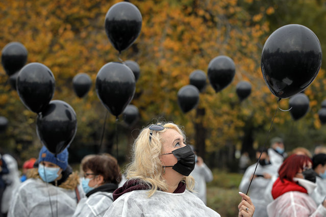 Medical workers, wearing masks for protection against the COVID-19 infection, hold black balloons in memory of those who lost their lives while in the care of the state health system in Bucharest, Romania, Tuesday, November 17, 2020. A fire last week at a hospital treating COVID-19 patients in northeastern Romania killed 11 people who were intubated in the intensive care unit. (Photo by Vadim Ghirda/AP Photo)