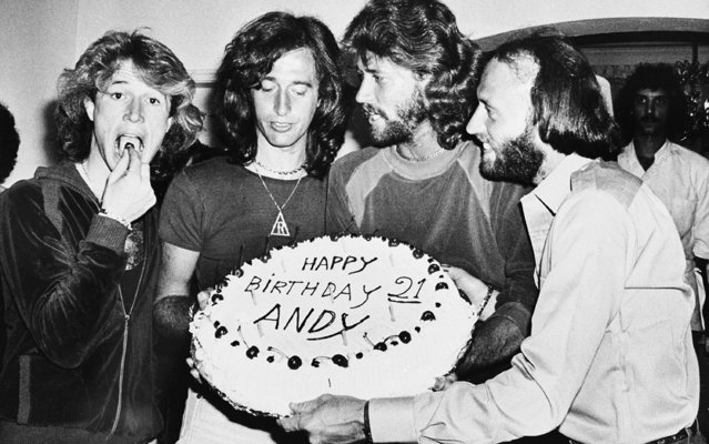 Andy Gibb eats a cherry from his birthday cake at a party given by his family in his home in Miami Beach, Fla., Monday night, March 6, 1979. Andy's brothers, the Bee Gees, from left are, Robin, Barry and Maurice. (Photo by AP Photo)