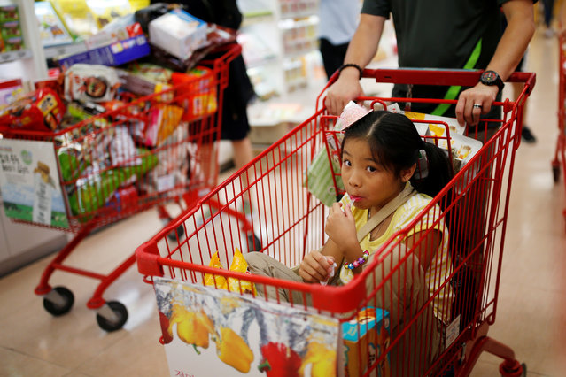 A man pushes her daughter on a cart as they shop at a market in Seoul, South Korea, July 26, 2016. (Photo by Kim Hong-Ji/Reuters)