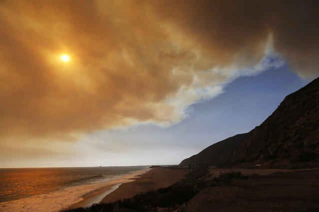 Smoke plums fill the sky over the Pacific Ocean from a wildfire burning towards Point Mugu on Pacific Coast Highway in Ventura County May 2, 2013. A wind-driven brush fire raging northwest of Los Angeles prompted the evacuation of hundreds of homes and a university campus on Thursday as flames engulfed several farm buildings and recreational vehicles at the fringe of threatened neighborhoods. (Photo by Patrick T. Fallon/Reuters)
