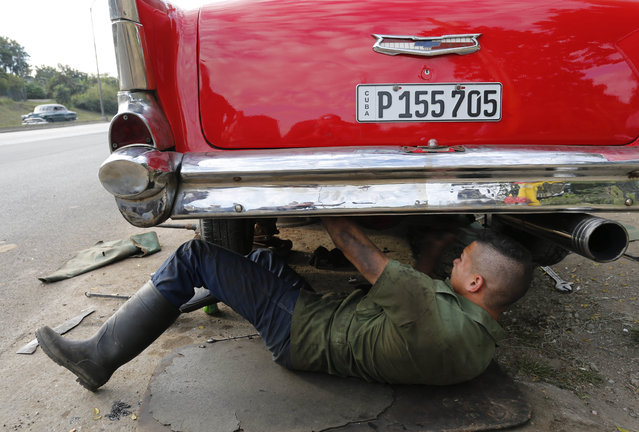 In this December 19, 2014 photo, a mechanic works under a vintage American car in Havana, Cuba.  U.S. car sales have been banned in Cuba since 1959. (Photo by Desmond Boylan/AP Photo)