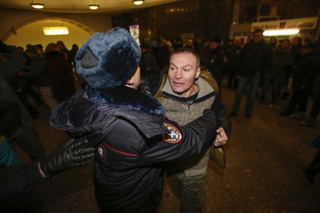 Police detain a protester during an unsanctioned protest in Manezhnaya Square in Moscow, Russia, Tuesday, December 30, 2014. (Photo by Denis Tyrin/AP Photo)