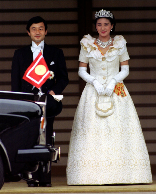 Crown Prince Naruhito and Crown Princess Masako step outside the Imperial Palace to their limousine, decorated with an imperial chrysanthemum emblem flag, as they set out for a royal wedding parade to the groom's Togu Palace residence, June 9, 1993. (Photo by John Pryke/Reuters)