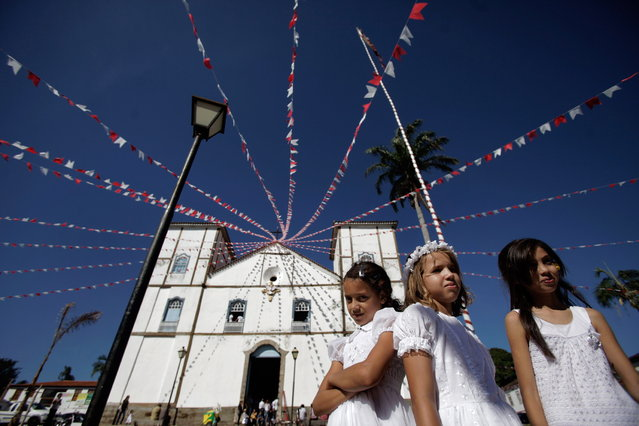 """Girls representing angels stand in front of Our Lady of the Rosary church, during the """"Cavalhadas"""" festival, in Pirenopolis, Brazil, Sunday, May 19, 2013. The popular festival is a tradition that was introduced in the 1800's by a Portuguese priest to mark the the ascension of Christ. The 3-day festival reenacts the Christian knights' defeat of the Moors. (Photo by Eraldo Peres/AP Photo)"""