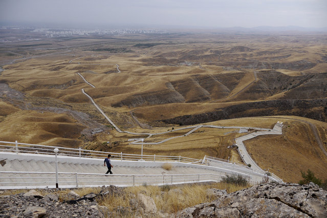 """The Serdar Health Path, winding into the hills south of Ashgabat. The 8km track features prominently in the country's annual """"Health Week"""". In 2000, former president Saparmurat Niyazov made an example of his entire cabinet, cheering them them on as they struggled their way up the path – he'd been flown to the top by helicopter. (Photo by Amos Chapple via The Atlantic)"""