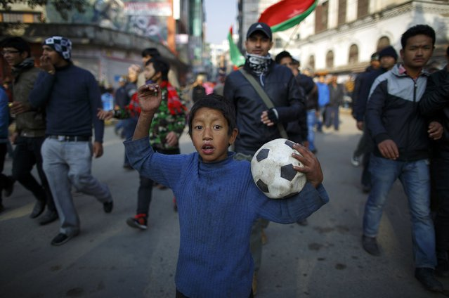 A boy holding a soccer ball takes part in a protest rally along the deserted road during the general strike independently called by the Unified Communist Party of Nepal (Maoist) and led by 30 party alliance and the Communist Party of Nepal (Maoist), demanding that the drafting of the new constitution is done on time through consensus, in Kathmandu January 13, 2015. (Photo by Navesh Chitrakar/Reuters)