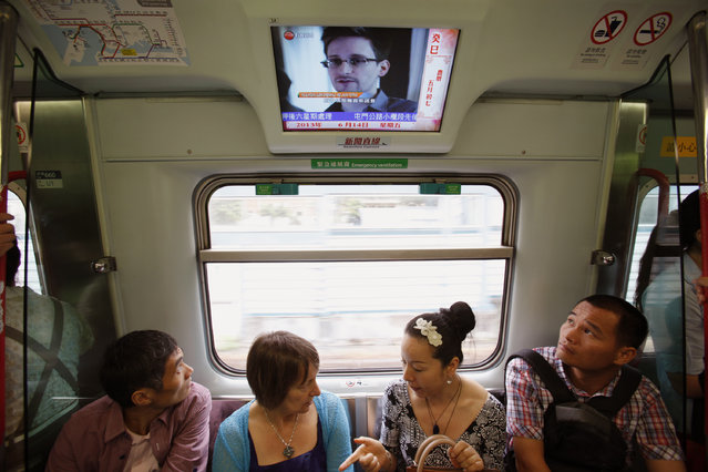 Passengers watch a television screen broadcasting news on Edward Snowden, a contractor at the National Security Agency (NSA), on a train in Hong Kong June 14, 2013. FBI Director Robert Mueller said on Thursday that the U.S. government is doing everything it can to hold confessed leaker Edward Snowden accountable for splashing surveillance secrets across the pages of newspapers worldwide. (Photo by Bobby Yip/Reuters)