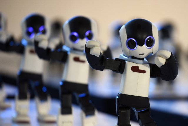 """A hundred humanoid robots named """"Robi"""" perform a dance during a promotional event for the launch of a weekly Robi Magazine in Tokyo, Japan, 20 January 2015. (Photo by Franck Robichon/EPA)"""
