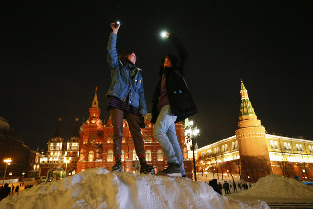 People shine their cellphone flashlights in support of jailed opposition leader Alexei Navalny and his wife Yulia Navalnaya near Red Square, Moscow, Russia, Sunday, February 14, 2021. (Photo by Alexander Zemlianichenko/AP Photo)