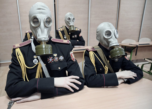 Children learn how to wear a gas mask at a military academy in Kiev. (Photo by Aude Osnowycz/The Guardian)
