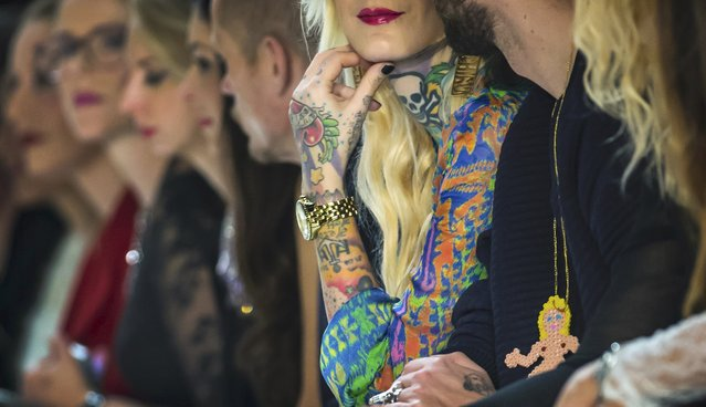 A tattooed woman sitting in the front row follows the show of designer Lena Hoschek at Berlin Fashion Week Autumn/Winter 2015 in Berlin January 20, 2015. (Photo by Hannibal Hanschke/Reuters)