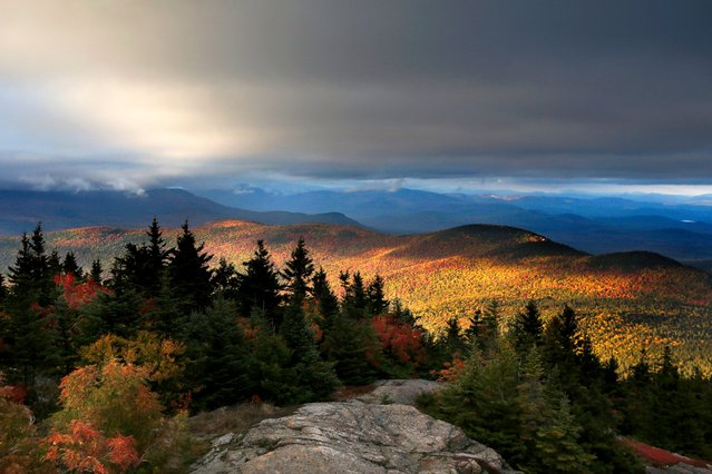 Fall foliage colors a line of mountains in Chatham, N. H., as unsettled weather begins to clear, October 4, 2016. The state's mountain regions are approaching their peak autumn colors. (Photo by Robert F. Bukaty/AP Photo)