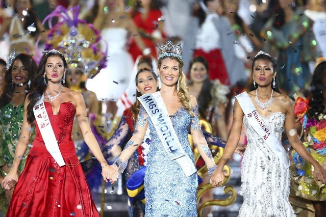 Miss World Mireia Lalaguna Royo from Spain, center, Sofia Nikitchuk from Russia, left, the runner-up, and Maria Harfanti from Indonesia, right, the second runner-up celebrate at the end of the 2015 Miss World Grand Final in Sanya in south China's Hainan province Saturday December 19, 2015. Spain's Mireia Lalaguna Royo was named the winner of the Miss World 2015 competition Saturday night in the southern Chinese island resort of Sanya, an event dogged by controversy over China's refusal to allow Canada's entrant to attend. (Photo by Chinatopix Via AP Photo)