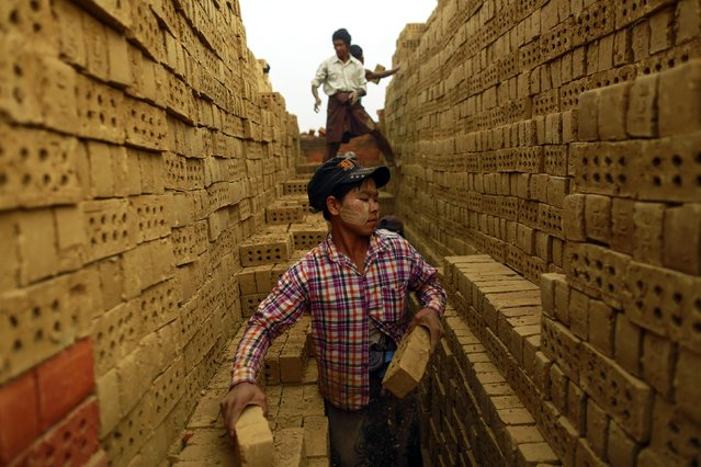 Workers stack bricks at a brick kiln, on the outskirts of Yangon February 1, 2015. (Photo by Soe Zeya Tun/Reuters)