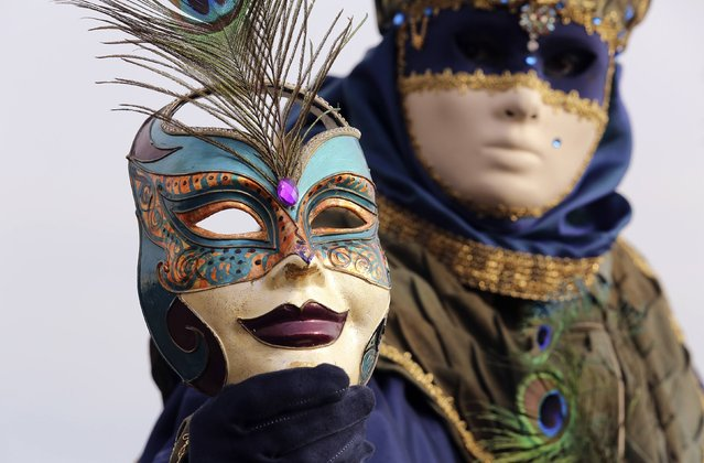 A masked reveller poses in front of St. Mark's square during the first day of carnival in Venice February 1, 2015. (Photo by Stefano Rellandini/Reuters)