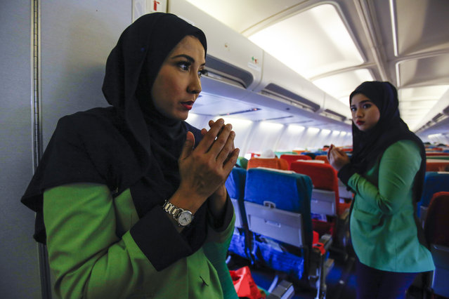 In this December 22, 2015, photo, Rayani Air flight crews prays before departure at Kuala Lumpur International Airport 2 in Sepang, Malaysia. The short domestic flight from Kuala Lumpur, Malaysia's biggest city, begins with a recital of Prophet Muhammad's supplication before his travel. (Photo by Joshua Paul/AP Photo)