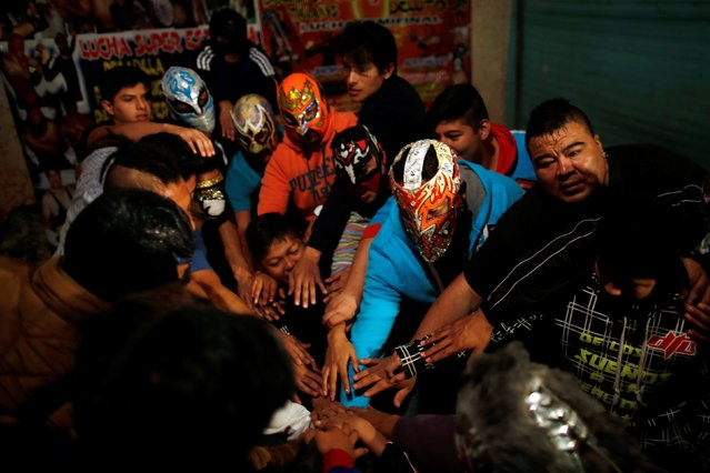 Wrestlers join hands before an extreme wrestling fight in a ring inside a car wash in Tulancingo Hidalgo, Mexico October 8, 2016. (Photo by Carlos Jasso/Reuters)