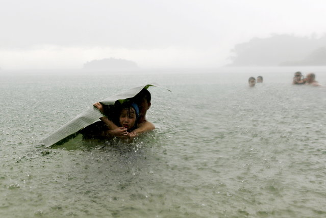 A young girl covers herself from the rain with a banana leaf next to a man in the sea on the outskirts of Colon City October 17, 2015. (Photo by Carlos Jasso/Reuters)