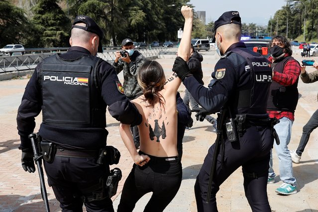 Policemen escort a Femen activist who broke into a rally of Franco's dictatorship regimen followers in Madrid, Spain, 28 March 2021. (Photo by Zipi/EPA/EFE)