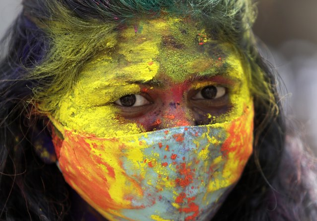 An Indian woman smeared in colors looks on during Holi festival in Mumbai, India, Monday, March 29, 2021. (Photo by Rajanish Kakade/AP Photo)