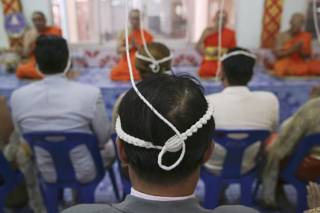 Couples wear ropes around their heads before stepping into a pink coffin during their wedding ceremony at Wat Takien temple in Nonthaburi province, on the outskirts of Bangkok February 14, 2015. (Photo by Damir Sagolj/Reuters)