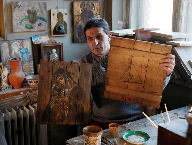 Ukrainian artist Oleksandr Klymenko shows his artwork and part of an ammunition box at a studio in Kyiv, Ukraine on March 26, 2021. Instead of using regular wooden panels, artists Sofia Atlantova and Oleksandr Klymenko paint icons on the covers and bottoms of ammunition boxes brought from the eastern Donbass region, the epicentre of Ukraine's conflict with Russian-backed separatists. (Photo by Gleb Garanich/Reuters)