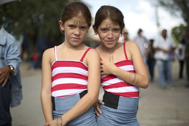 Sisters await the arrival of the caravan carrying the late Cuban President Fidel Castro's ashes in El Maja, Cuba, December 1, 2016. (Photo by Edgard Garrido/Reuters)
