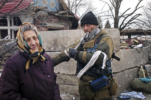 A pro-Russian rebel takes a ribbon from his arm in Debaltseve, eastern Ukraine on Thursday, February 19, 2015. (Photo by Peter Leonard/AP Photo)