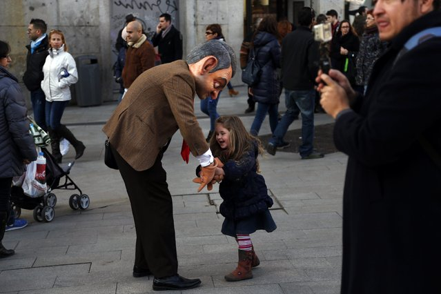 A girl plays with a street performer dressed as the British television series character Mr. Bean at Madrid's Puerta del Sol square February 19, 2015. (Photo by Susana Vera/Reuters)