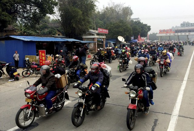 Migrant workers ride their motorcycles with families and friends, as they make their way home for the upcoming Spring Festival, on a hazy day in Fengkai county, Guangdong province, February 12, 2015. From the start of the travel rush period due to the coming Chinese Lunar New Year. (Photo by Reuters/China Daily)