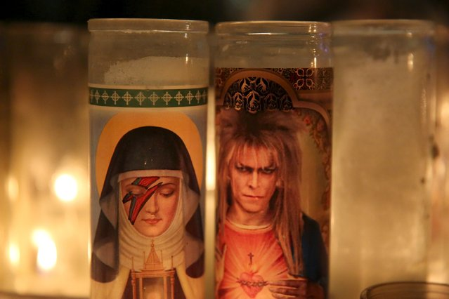 Candles are seen at a memorial for deceased musician David Bowie outside his former residence in the Manhattan borough of New York January 14, 2016. (Photo by Andrew Kelly/Reuters)
