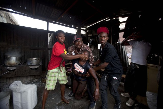 People help a street vendor who took refuge inside a restaurant to escape tear gas being fired by police breaking up a protest in Port-au-Prince, Haiti, on September 30, 2013. Police broke up the end of an anti-government demonstration by people marking the anniversary of the 1991 ouster of former President Jean-Bertrand Aristide. (Photo by Dieu Nalio Chery/Associated Press)