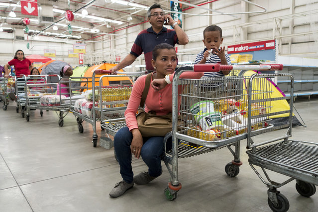 People line up to pay inside a Makro supermarket in Caracas, January 9, 2015. (Photo by Jorge Silva/Reuters)