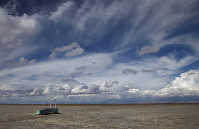 In this January 12, 2016 photo, an abandoned boat lies on the dried up lake bed of Lake Poopo, on the outskirts of Untavi, Bolivia. Drought caused by the recurrent El Nino meteorological phenomenon is considered the main driver of the lake's demise. Along with glacial melting, authorities say another factor is the diversion of water from Poopo's tributaries, mostly for mining but also for agriculture. (Photo by Juan Karita/AP Photo)