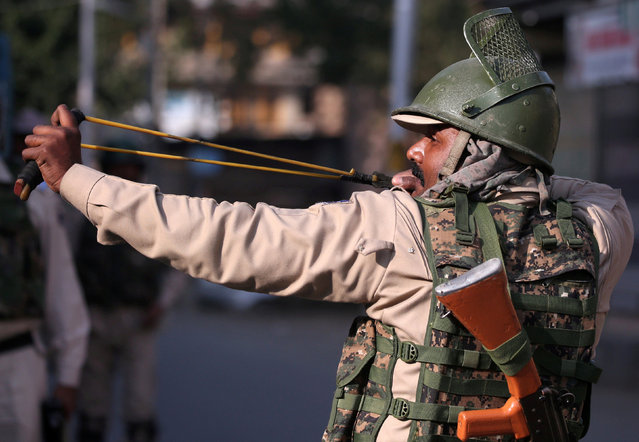 An Indian policeman uses a slingshot during clashes with Kashmiri demonstrators (not pictured) during a protest in downtown Srinagar October 12, 2018. (Photo by Danish Ismail/Reuters)