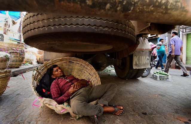 A truck driver naps under his truck at the fancy bazaar area during the twelve hours Assam bandh or strike in Guwahati, Assam, India, 23 October 2018. At least 46 organisations are observing a 12-hour bandh across the state to protest against the Centre's bid to clear the Citizenship (Amendment) Bill 2016, in the Winter Session of Parliament. (Photo by EPA/EFE/Stringer)