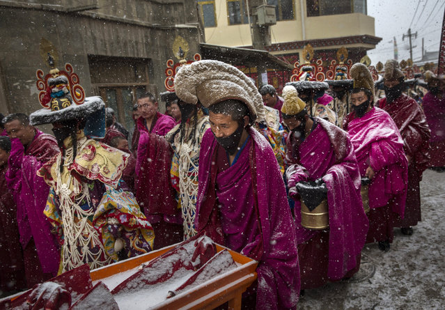 Tibetan Buddhist monks of the Gelug, or Yellow Hat order, are covered in snow as they take part in a procession during Monlam or the Great Prayer rituals on March 4, 2015 at the Labrang Monastery, Xiahe County, Amdo, Tibetan Autonomous Prefecture, Gansu Province, China. (Photo by Kevin Frayer/Getty Images)